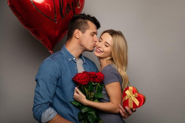 Feche a foto de um doce casal, que está comemorando o dia dos namorados dando presentes um ao outro e sorrindo de felicidade.