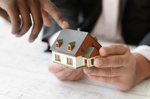 Feche a foto de um empreiteiro caucasiano segurando um projeto imobiliário enquanto seu colega africano apontando o dedo para o edifício da maquete, explicando o projeto durante a reunião de apresentação no escritório