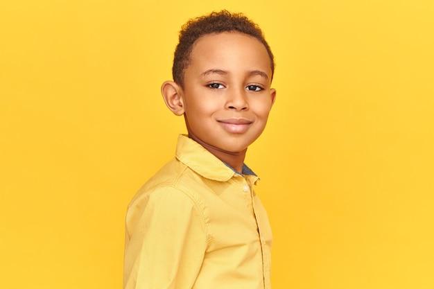 Feche a foto de um garoto bonito e amigável com uma camisa amarela, sorrindo e de bom humor, posando isolado contra um fundo em branco com espaço de cópia