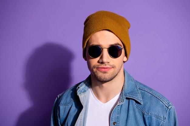 Feche a foto de um hipster legal sério e confiante olhando francamente para a câmera através de óculos de sol isolados sobre um fundo brilhante