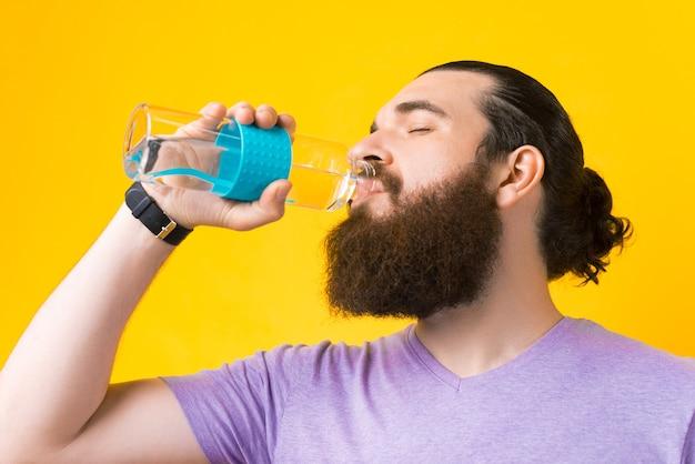 Feche a foto de um homem barbudo bebendo água de uma garrafa de vidro sobre o fundo amarelo