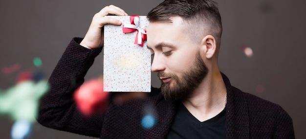 Feche a foto de um homem com barba segurando um presente no ombro, posando em uma parede cinza com confete