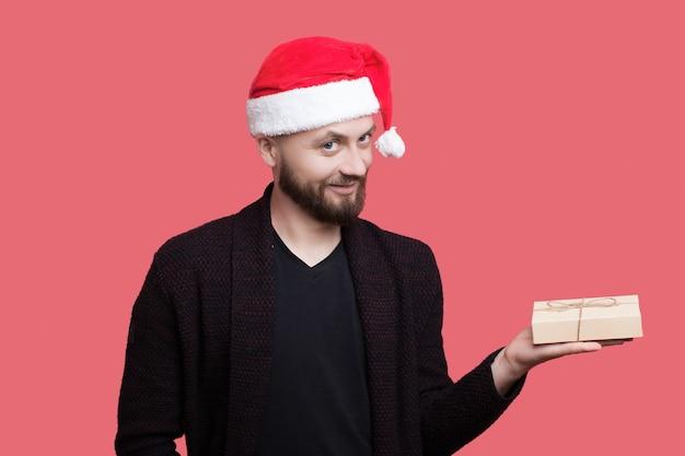 Feche a foto de um homem generoso com chapéu de papai noel e barba segurando um presente e sorria para a câmera com roupas casuais