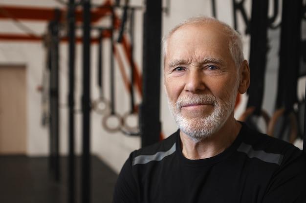 Feche a foto de um homem maduro de setenta anos de idade, caucasiano, com rugas, olhos azuis e barba densa, vestindo uma camiseta preta elegante enquanto se exercita na academia sozinho, olhando para a câmera