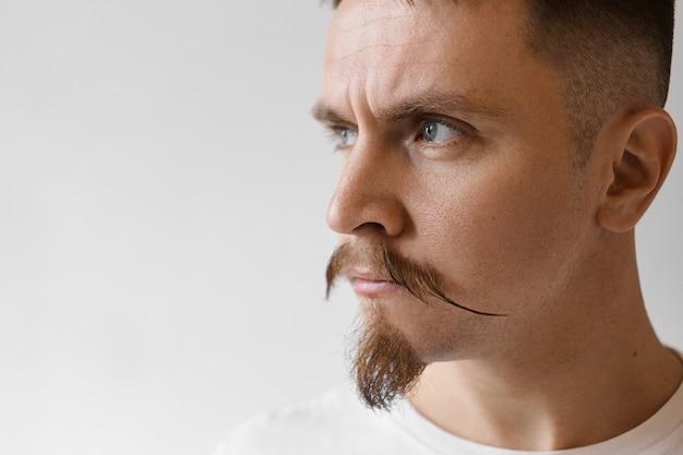 Feche a foto de um jovem bonito sombrio com barba estilosa e bigode franzido, com olhar irritado e mal-humorado, sendo insultado com algumas palavras ofensivas após uma briga com a namorada