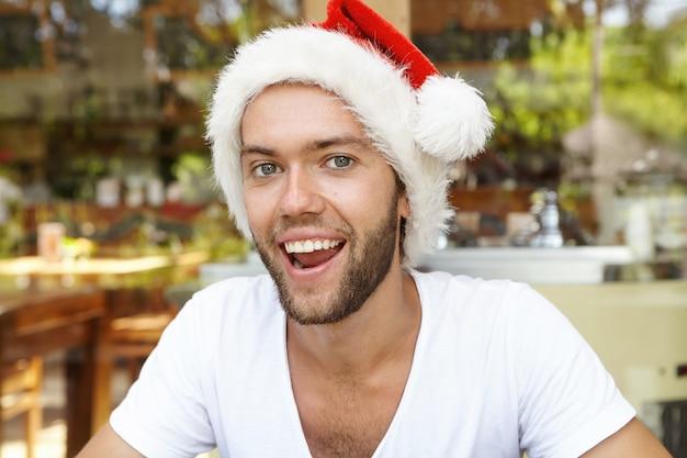 Feche a foto de um jovem hippie feliz com uma barba estilosa, vestindo camiseta branca e chapéu vermelho de papai noel, celebrando o natal em um país tropical quente, relaxando no café contra um fundo desfocado