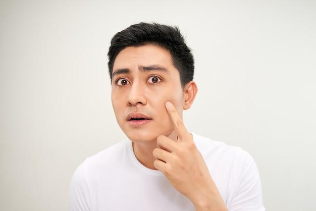 Feche a foto de um jovem procurando por acnes no rosto