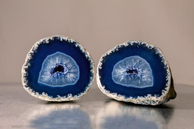 Feche a foto de um mineral de ágata azul em uma superfície reflexiva. a ágata tem uma estrutura zoneada típica e é visível até a olho nu.