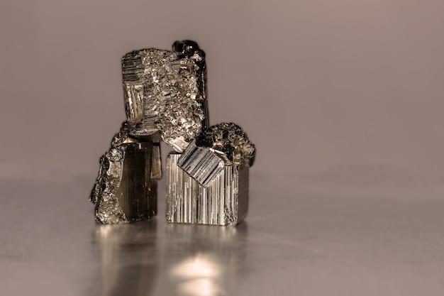 Feche a foto de um mineral de pirita na superfície reflexiva. ocorre em cristais cúbicos, pentagonododecaédricos ou octaédricos, às vezes com faces alternadas estriadas longitudinalmente