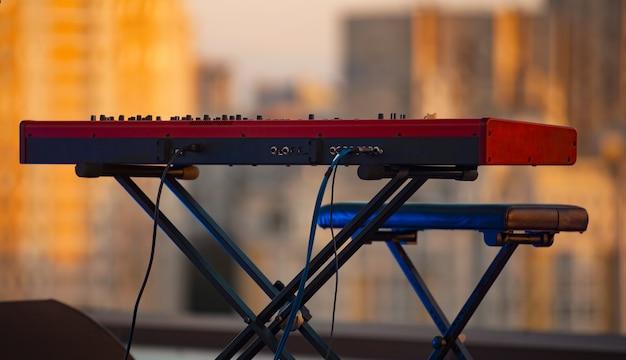 Feche a foto de um piano eletrônico vermelho sentado no telhado, antes do show