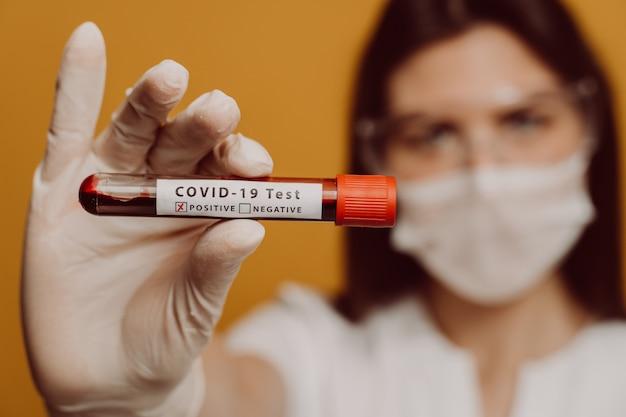 Feche a foto de um tubo covid-19 positivo marcado em uma mão de enfermeira na luva. exame de sangue durante a pandemia de coronavírus. médicos, infectologista, pesquisa e conceito covid19.