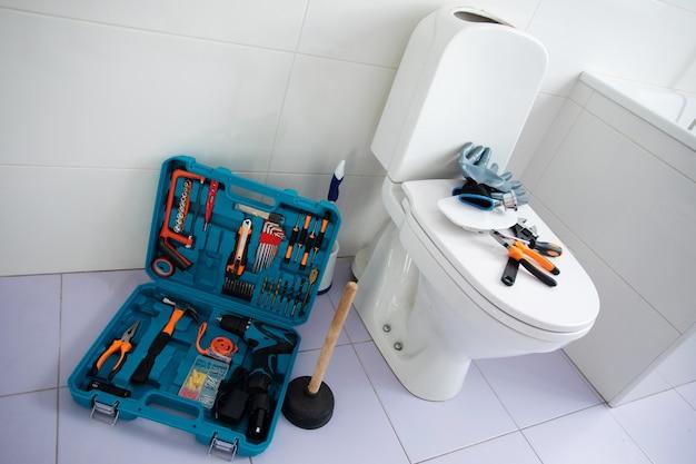 Feche a foto de um vaso sanitário de cerâmica em um banheiro doméstico com uma caixa de ferramentas