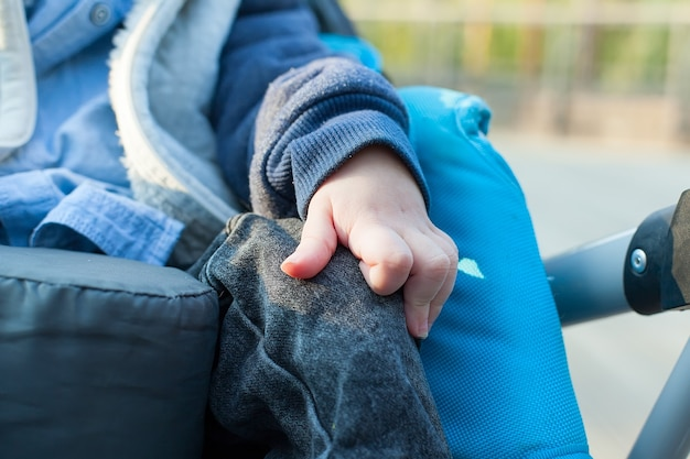 Feche a foto de uma criança com deficiência sentada na cadeira de rodas no hospital a pé, sua mão controlando a roda, a vida na idade de educação de crianças especiais, o conceito de criança com paralisia cerebral feliz.