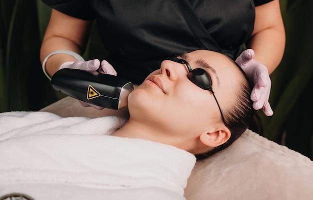 Feche a foto de uma depilação facial com laser usando um dispositivo moderno em uma clínica de bem-estar