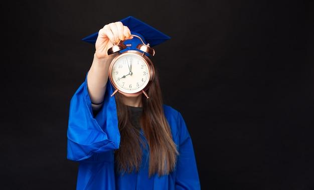 Feche a foto de uma estudante com um manto azul mostrando o despertador