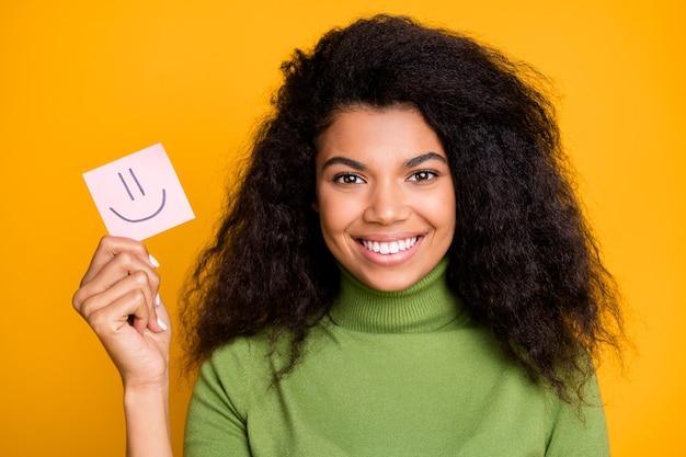 Feche a foto de uma garota alegre e radiante mostrando um papel com um emoji pintado, comparando as emoções isoladas com um fundo de cor vibrante