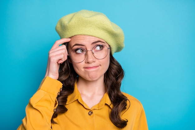Feche a foto de uma garota insegura arranhar o dedo na testa olhar copyspace pense não sei resposta não posso decidir a decisão escolha a escolha usar roupas amarelas toucas isolado fundo de cor azul