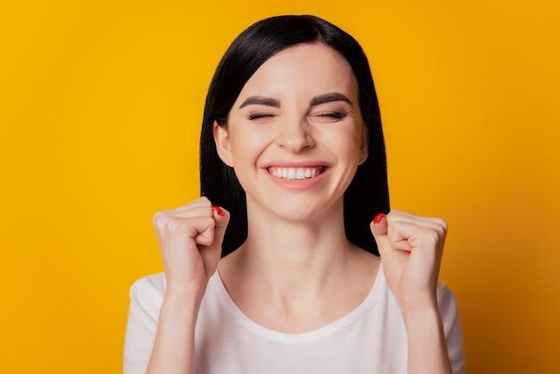 Feche a foto de uma garota louca e funky fã de esportes comemorar a vitória do time de futebol, levantar os punhos e gritar, sim, usar uma roupa bonita isolada sobre um fundo de cores vivas