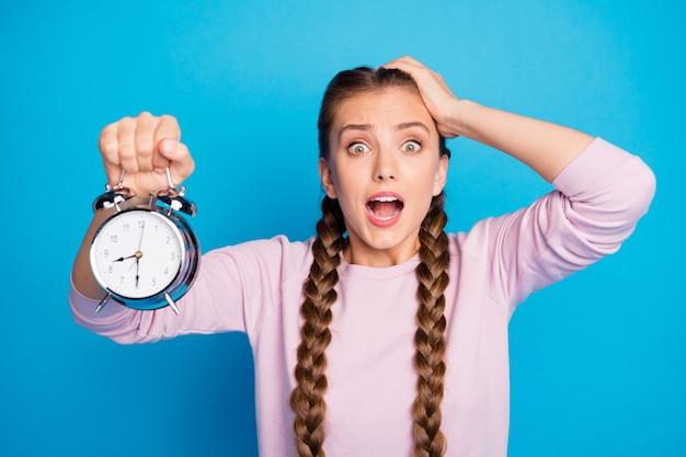 Feche a foto de uma jovem ansiosa e preocupada com tranças, rabos de cavalo, dormindo demais, segure o relógio, encontre ela atrasada, sinta-se frustrada, grite, use roupas estilo casual isolado fundo de cor