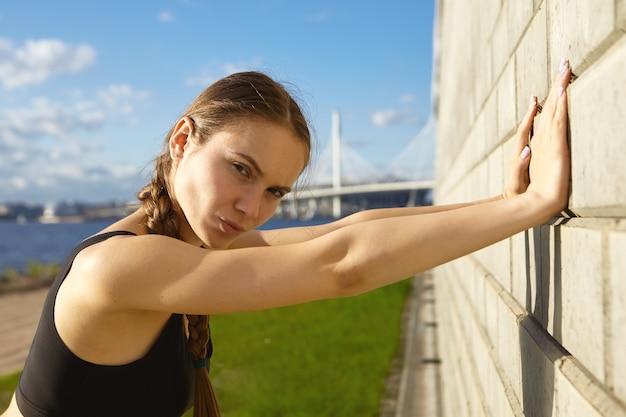 Feche a foto de uma jovem desportista séria e autodeterminada com braços fortes, posando perto de uma parede de tijolos com céu azul e rio
