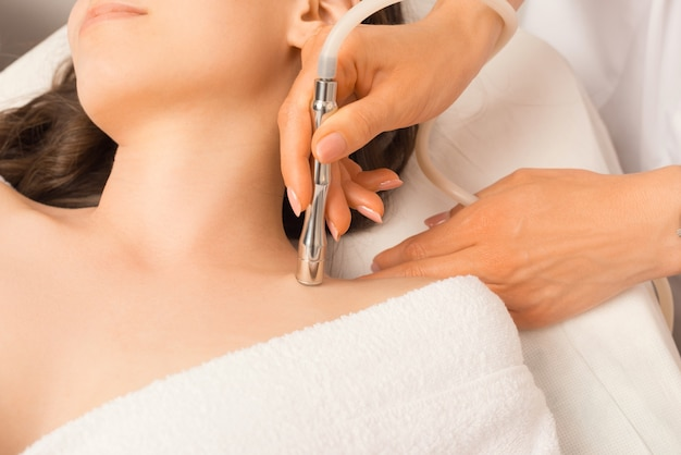 Feche a foto de uma jovem fazendo um tratamento de pele com vácuo no cosmetologista