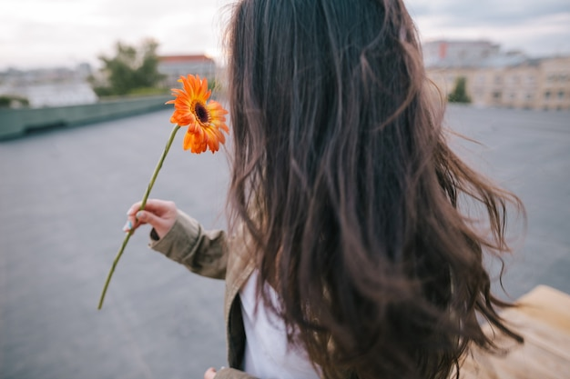 Feche a foto de uma jovem irreconhecível com flor de laranjeira no fundo urbano da cidade. encontro no telhado, liberdade e sonhos românticos, felicidade e conceito de amor