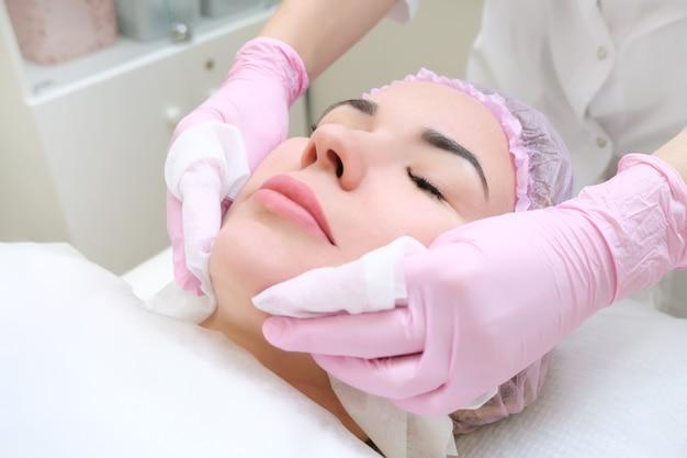 Feche a foto de uma linda jovem com os olhos fechados, recebendo o procedimento de limpeza facial no salão de beleza.