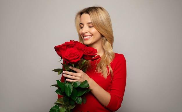 Feche a foto de uma linda mulher com uma roupa vermelha, que está posando na frente, segurando um buquê de rosas vermelhas e sorrindo com os olhos fechados.