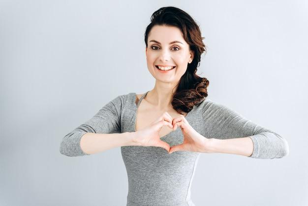 Feche a foto de uma linda senhora incrível mostra o coração com os dedos.