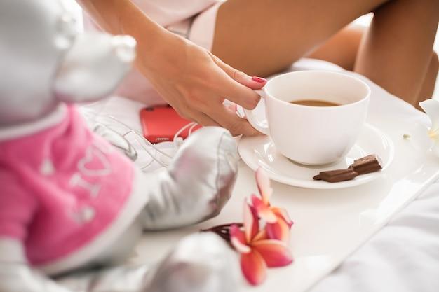 Feche a foto de uma mão de mulher com uma xícara de café e um prato com um pedaço de chocolate ao leite em cima da cama. manhã feliz