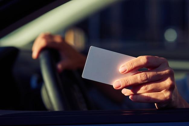 Feche a foto de uma mão feminina segurando um cartão de plástico em branco de uma mulher sentada no carro e mostrando o motorista