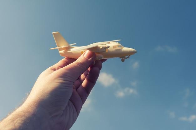 Feche a foto de uma mão masculina segurando um avião de brinquedo contra o céu azul
