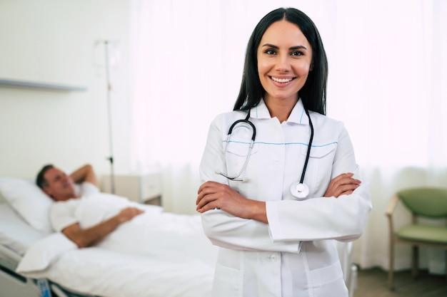 Feche a foto de uma médica sorridente, confiante e fofa, usando um casaco com um estetoscópio e o paciente na cama,