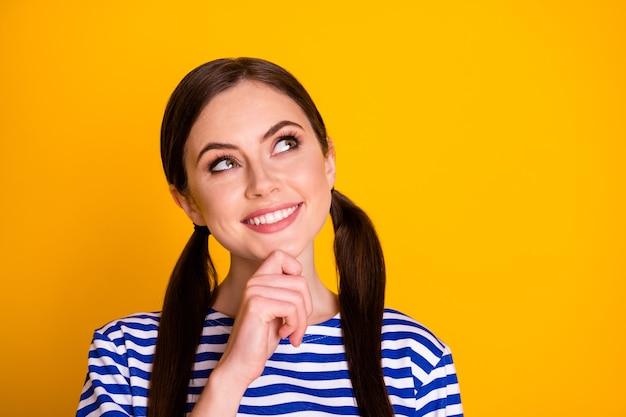 Feche a foto de uma menina alegre e pensativa, olhe copyspace toque queixo dedo pense pensamentos plano fins de semana de verão usar blusa listrada isolada sobre um fundo de cor brilhante