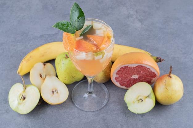 Feche a foto de uma mistura de coquetel de suco de frutas e frutas da estação.
