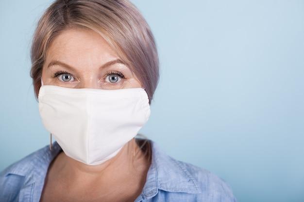 Feche a foto de uma mulher caucasiana com cabelo loiro usando uma máscara médica na parede azul com espaço livre