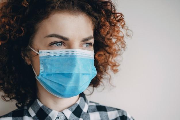 Feche a foto de uma mulher caucasiana com cabelo ruivo cacheado usando uma máscara médica durante o período de pandemia