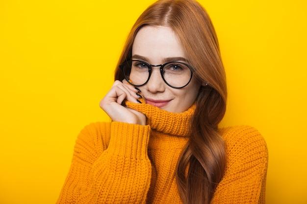 Feche a foto de uma mulher caucasiana com cabelos lisos e sardas, usando óculos e suéter laranja sobre fundo amarelo