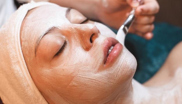 Feche a foto de uma mulher caucasiana com olhos fechados, tendo uma máscara facial branca no centro de spa