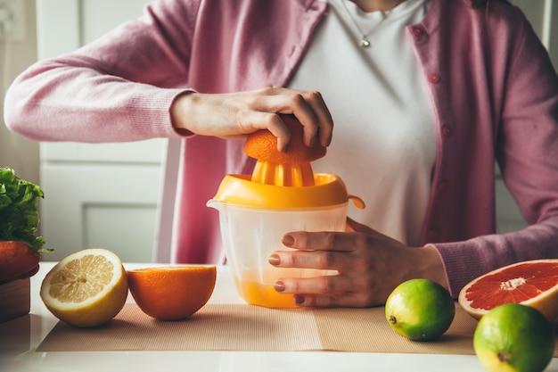 Feche a foto de uma mulher com hábitos saudáveis espremendo suco de laranja e limão na cozinha