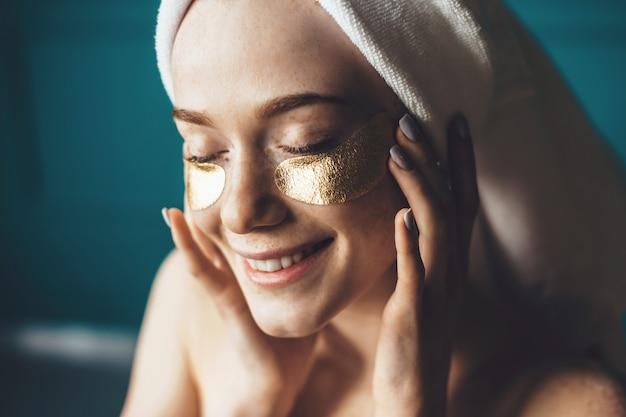 Feche a foto de uma mulher de sardas usando tapa-olhos dourados, cobrindo a cabeça com uma toalha e sorria