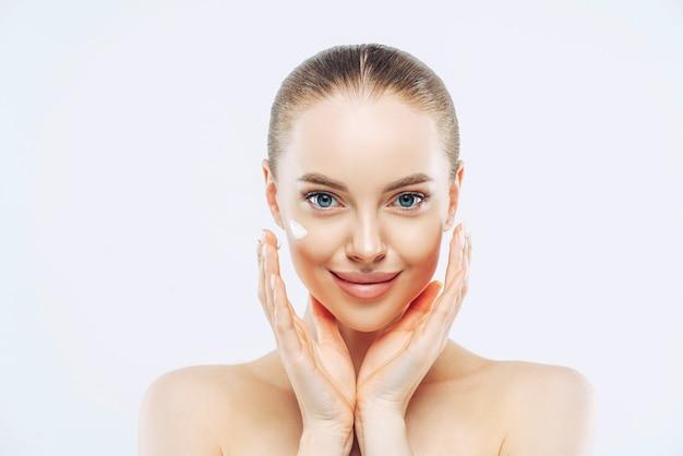 Feche a foto de uma mulher jovem e atraente nua com cabelo penteado, aplica creme ou loção facial, toca o rosto, tem maquiagem natural, posa contra um fundo branco, cuida da pele.