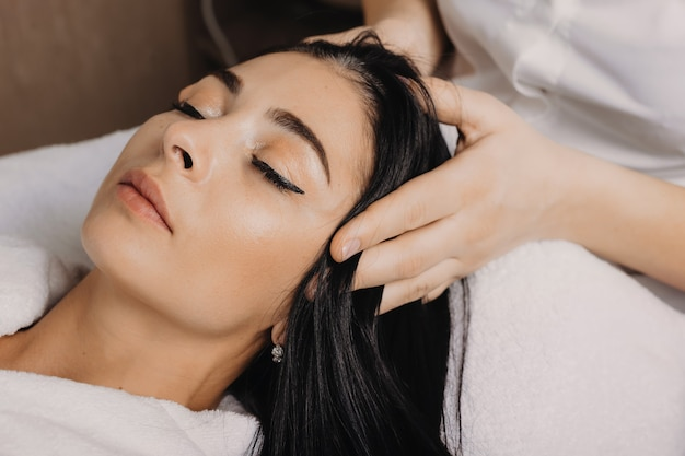 Feche a foto de uma mulher morena caucasiana deitada com os olhos fechados enquanto faz uma massagem na cabeça no salão spa