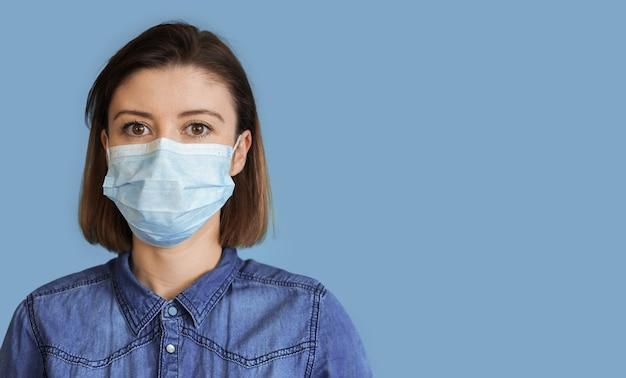 Feche a foto de uma mulher morena usando uma máscara médica em uma parede azul com espaço livre