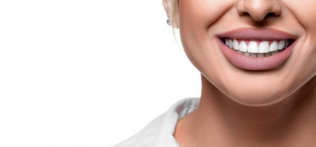 Feche a foto de uma mulher sorrindo. clareamento dos dentes e saúde bucal.