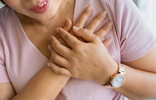 Feche a foto de uma mulher usando a mão para um buraco no peito com dor e sofre de uma doença cardíaca no rosto. conceito de infarto do miocárdio com elevação do segmento st.
