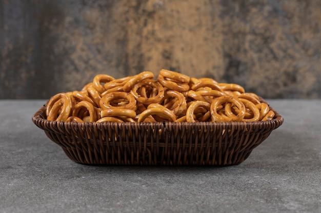 Feche a foto de uma pilha de biscoitos em forma de anel dentro da cesta