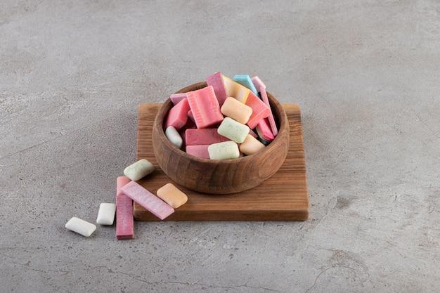 Feche a foto de uma pilha de chicletes coloridos em uma tigela de madeira