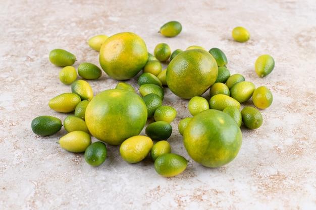 Feche a foto de uma pilha de tangerina e kumquats