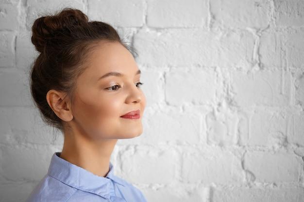 Feche a foto de uma secretária jovem atraente e alegre com um nó de cabelo e maquiagem brilhante, bebendo café ou chá, olhando e sorrindo alegremente